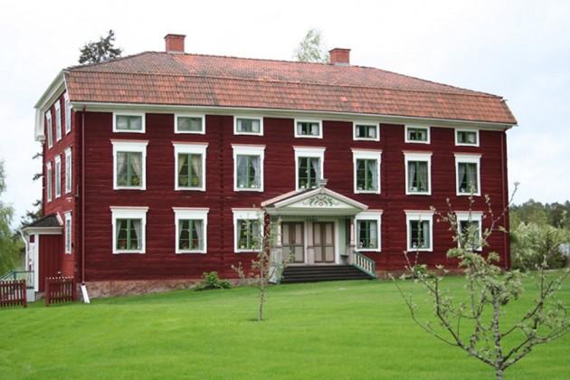 Ståtligt rött trähus med vita knutar i Hälsingland, Sverige.