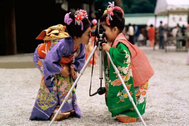 Två japanska flickor i vackra kimonos som tar kort på varandra.