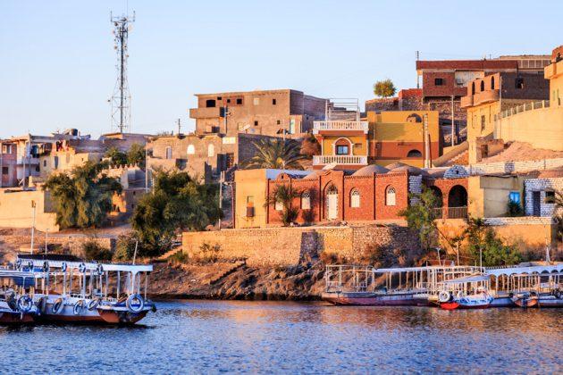 Aswan, Egypten, i kvällssol sett från Nilen.