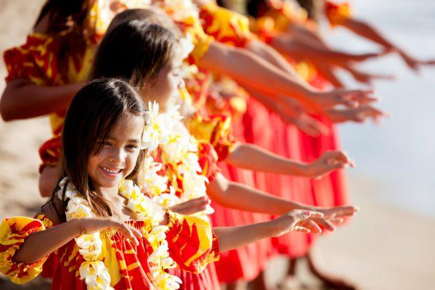 Glada barn som dansar med Hawaiikransar runt halsen.