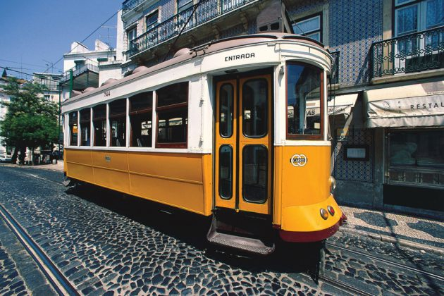 Gul spårvagn på gata i Lissabon, Portugal.