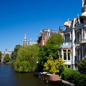 Kanal, fint omgärdad av grönska och vackra hus, i Amsterdam.