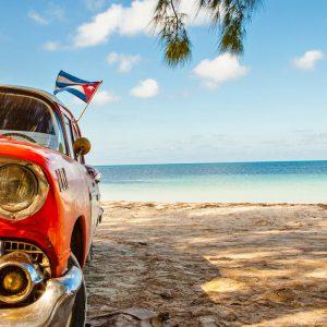Röd bil på strand på Kuba.